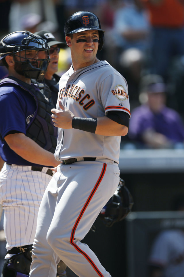Photo - San Francisco Giants' Andrew Susac, front, scores on a double by Hunter Pence as Colorado Rockies catcher Michael McKenry looks on in the eighth inning of the Giants' 4-2 victory in a baseball game in Denver on Monday, Sept. 1, 2014. The game was resumed in the bottom of the sixth inning of play when it was suspended because of rain on May 22. (AP Photo/David Zalubowski)