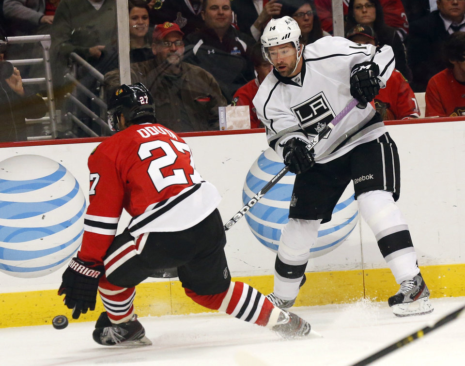 Photo - Chicago Blackhawks defenseman Johnny Oduya (27), of Sweden, deflects Los Angeles Kings right wing Justin Williams' shot on goal during the first period of an NHL hockey game, Monday, March 25, 2013, in Chicago. (AP Photo/Charles Rex Arbogast)