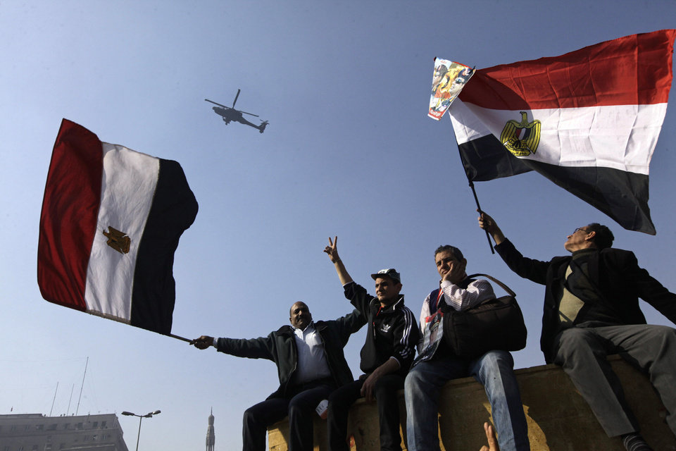 Photo - Egyptians wave national flags as they greet an army helicopter flying over Tahrir Square, the focal point of Egyptian uprising, in Cairo, Egypt, Saturday, Jan. 25, 2014. As Egyptians mark the third anniversary of their spectacular revolt against autocrat Hosni Mubarak in the name of democracy on Saturday, there has been a powerful sign of the country's stunning reversals since: letters of despair by some of the prominent activists who helped lead the uprising, leaked from the prisons where they are now jailed. (AP Photo/Amr Nabil)