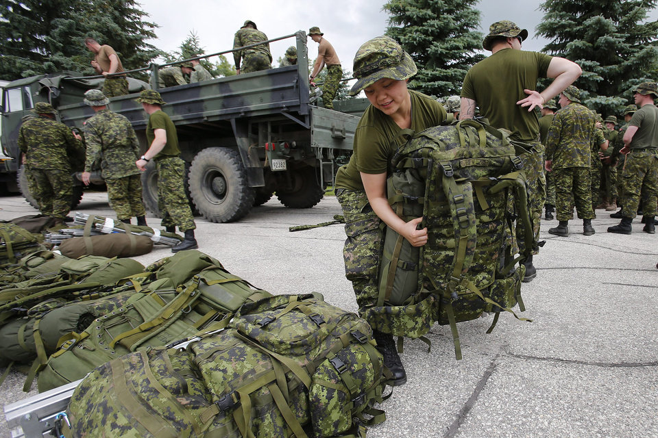 Photo - Military reserves arrive to assist with flood preparation at Southport, Manitoba, Saturday, July 5, 2014. Tropical storm Arthur hit Canada's Maritime provinces with near-hurricane strength winds and torrential rains, knocking out power to nearly 200,000 customers. (AP Photo/The Canadian Press, John Woods)