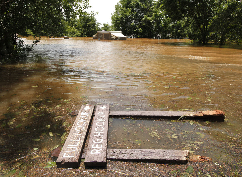 Photo - A Central State Park campground flooded before the owner could get this pop-up camper out of the area. The floodwater knocked down signs. PHOTO BY PAUL HELLSTERN, THE OKLAHOMAN.  PAUL HELLSTERN - THE OKLAHOMAN
