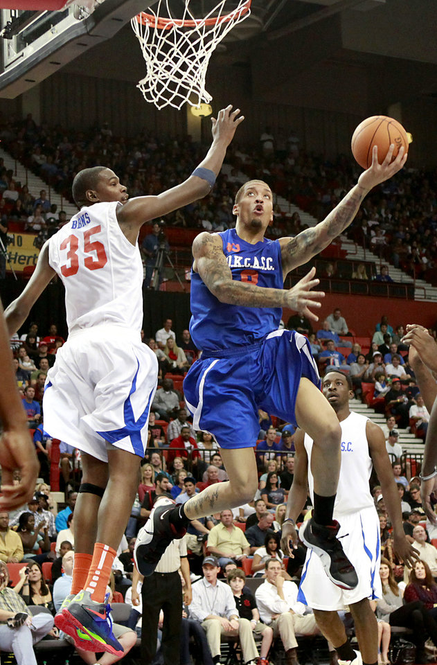 Photo - Michael Beasley (right) puts up a shot in front of Kevin Durant during the US Fleet Tracking Basketball Invitational at the Cox Convention Center in Oklahoma City Sunday, Oct. 23, 2011. The White Team defeated the Blue Team 176-171. Photo by John Clanton, The Oklahoman
