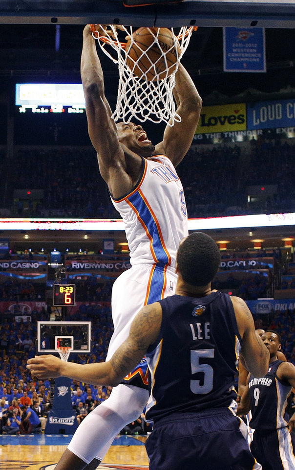 Photo - Oklahoma City's Serge Ibaka (9) dunks the ball over Memphis' Courtney Lee (5) during Game 1 in the first round of the NBA playoffs between the Oklahoma City Thunder and the Memphis Grizzlies at Chesapeake Energy Arena in Oklahoma City, Saturday, April 19, 2014. Photo by Nate Billings, The Oklahoman