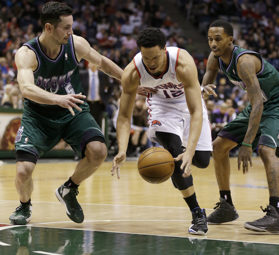 Photo - Atlanta Hawks' John Jenkins (12) drives between Milwaukee Bucks' J.J. Redick, left, and Brandon Jennings, right, during the first half of an NBA basketball game Saturday, Feb. 23, 2013, in Milwaukee. (AP Photo/Jeffrey Phelps)