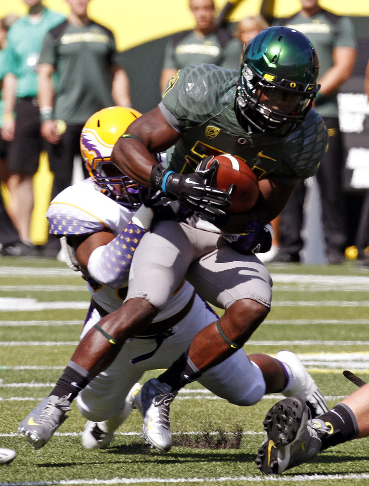 Photo -   Oregon running back Kenjon Barner, right, fights for yardage against Tennessee Tech defender Howard Griffin during the first half of their NCAA college football game in Eugene, Ore., Saturday, Sept. 15, 2012. (AP Photo/Don Ryan)