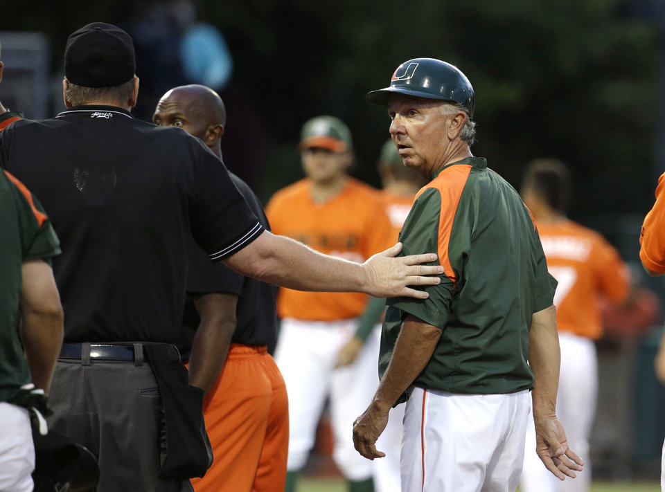 Photo - Miami head coach Jim Morris, right, is lead away by an umpire after the benches cleared between Miami and Texas Tech in the third inning during an NCAA college baseball regional tournament in Coral Gables, Fla., Sunday, June 1, 2014.  (AP Photo/Lynne Sladky)