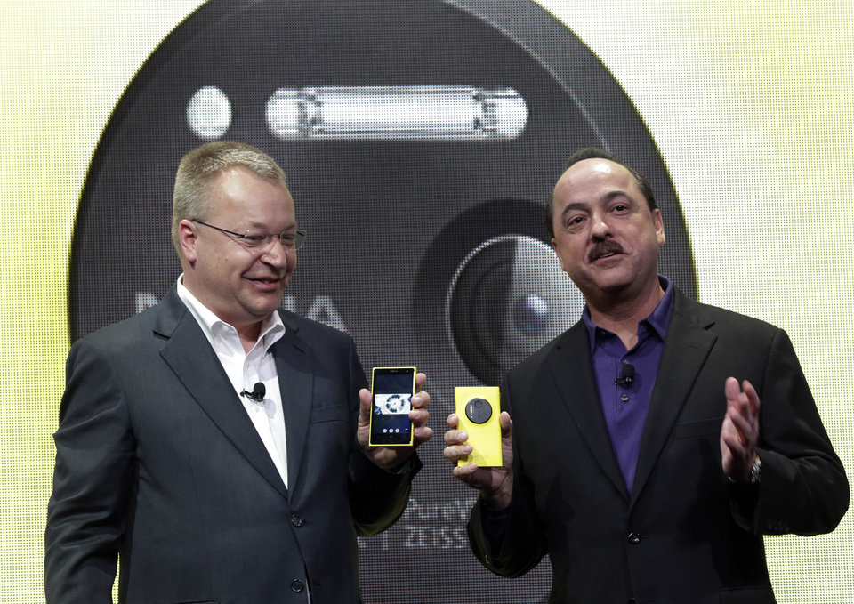 Photo - Nokia CEO Stephen Elop, left, and AT&T Mobility CEO Ralph de la Vega talk about the Nokia Lumia 1020 during its introduction, in New York,  Thursday, July 11, 2013. The Nokia Lumia 1020, with a 41-megapixel camera, records more detail than other camera phones and even tops point-and-shoot cameras. (AP Photo/Richard Drew)