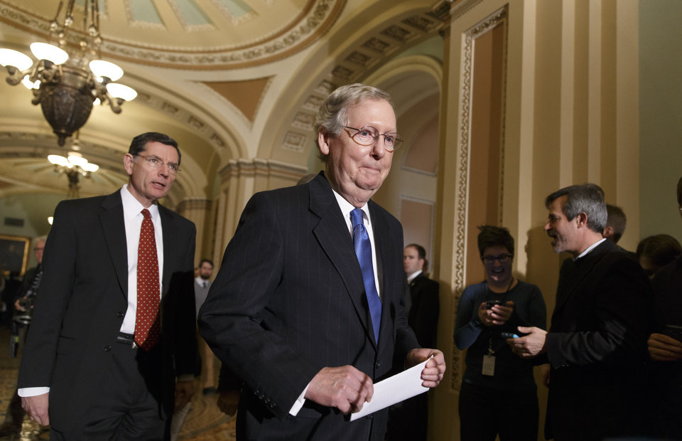 Photo - Senate Minority Leader Mitch McConnell, of Ky., right, accompanied by Sen. John Barrasso, R-Wyo., the Republican Policy Committee chairman, arrives to tell reporters that Senate Majority Leader Harry Reid of Nev., and his political tactics are almost entirely responsible for making the Senate dysfunctional, following a procedural vote on legislation to renew jobless benefits for the long-term unemployed, Tuesday, Jan. 7, 2014, on Capitol Hill in Washington.  (AP Photo/J. Scott Applewhite)