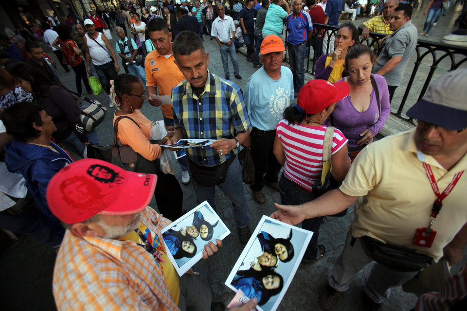 Photo - A man sells prints at 20 bolivars each, about 3.00 U.S. dollars, of one of the photographs released Friday by the Venezuelan government showing President Hugo Chavez with his daughters Maria Gabriela, left, and Rosa Virginia, right, at Bolivar square in Caracas, Venezuela, Friday, Feb. 15, 2013. Amid widespread speculation and rumors in Venezuela about Chavez's delicate condition following his Dec. 11 cancer surgery, the government released the first photos of the ailing president in more than two months on Friday, presenting images of him smiling alongside his daughters in Cuba. (AP Photo/Fernando Llano)