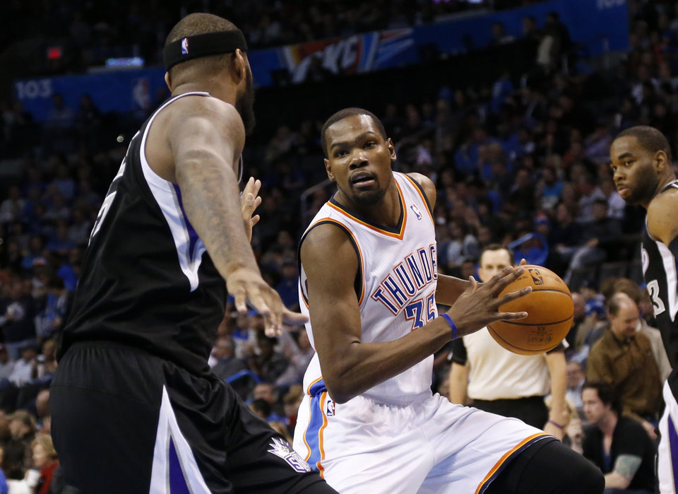 Photo - Oklahoma City Thunder forward Kevin Durant (35) drives around Sacramento Kings center DeMarcus Cousins (15) in the third quarter of an NBA basketball game in Oklahoma City, Sunday, Jan. 19, 2014. Oklahoma City won 108-93.(AP Photo/Sue Ogrocki)