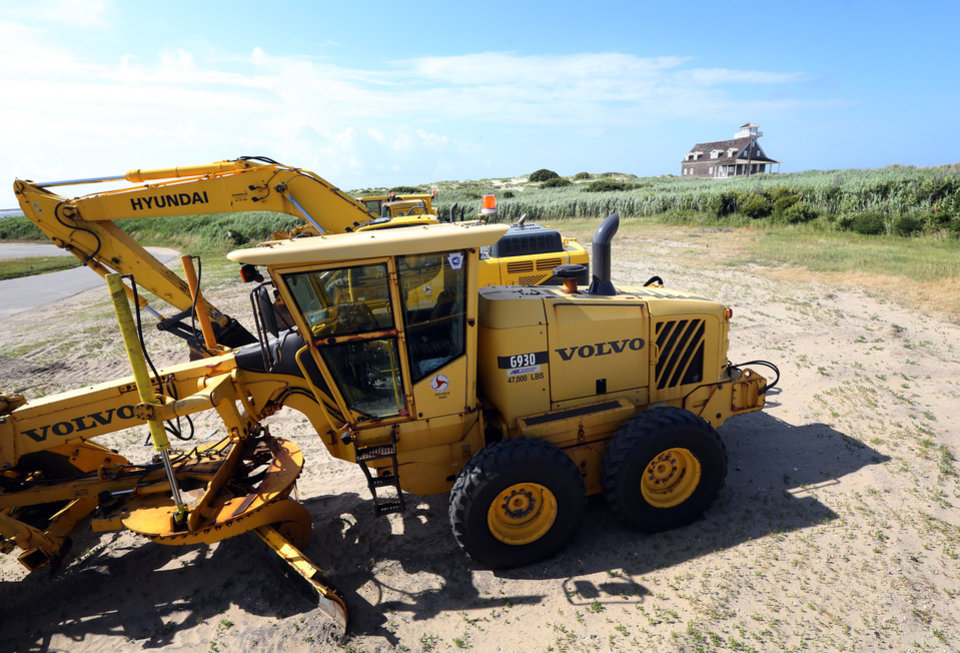 Photo - Road clearing equipment is staged near the old Coast Guard Station at the north end of Hatteras Island, N.C., to prepare for the approaching Tropical Storm Arthur on Wednesday, July 2, 2014. The storm, which is forecast to reach hurricane strength by the time it approaches the Outer Banks on Friday, could push mountains of sand onto Highway 12, the road that leads off the island. (AP Photo/The Virginian-Pilot, Steve Earley)