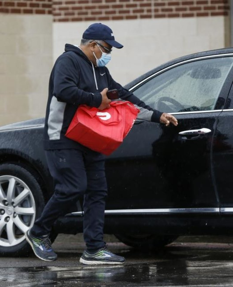 Photo -  A food delivery driver wearing a mask gets back in his car Monday after a stop in the Belle Isle Station shopping center in Oklahoma City. [Nate Billings/The Oklahoman]
