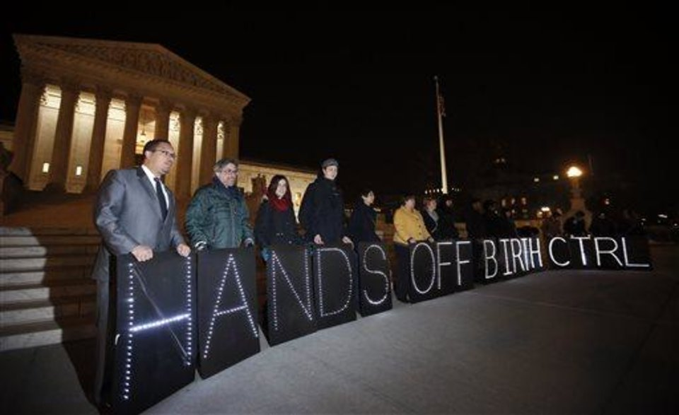 "Photo - A group of people organized by the NYC Light Brigade and the women's rights group UltraViolet, use letters in lights to spell out their opinion, in front of the Supreme Court, Monday, March 24, 2014 in Washington. Holding the ""H"" in ""Hands"" at left, is Rep. Keith Ellison, D-Minn. The Supreme Court is weighing whether corporations have religious rights that exempt them from part of the new health care law that requires coverage of birth control for employees at no extra charge. (AP Photo/Alex Brandon)"