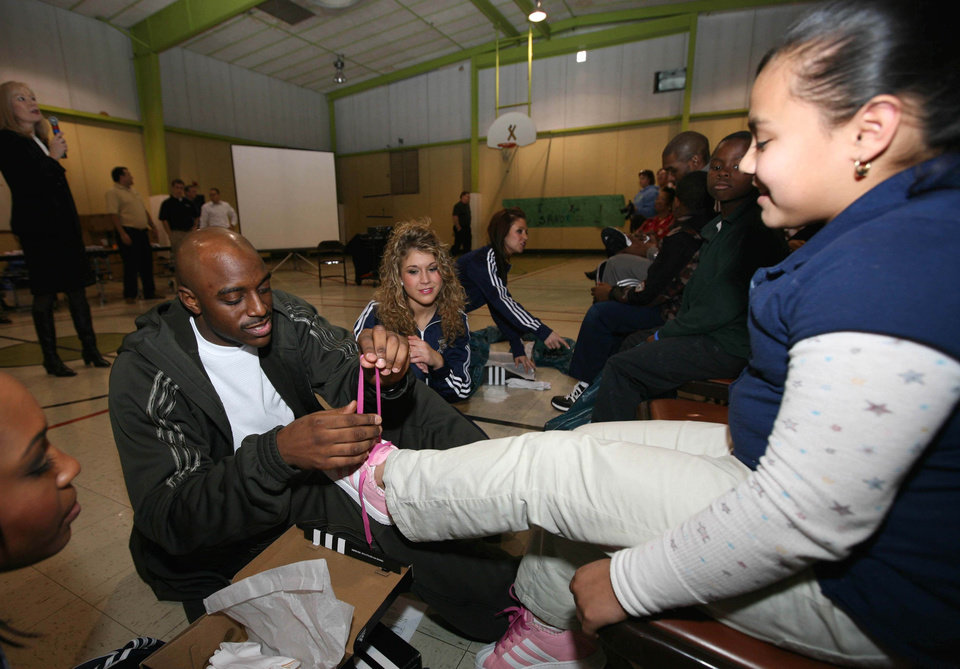 Photo - NBA BASKETBALL PLAYER: Oklahoma City Thunder guard Damien Wilkins puts a new pair of Adidas tennis shoes on the feet of a student at Dunbar Elementary School on Monday.  ORG XMIT: 0812152153543589