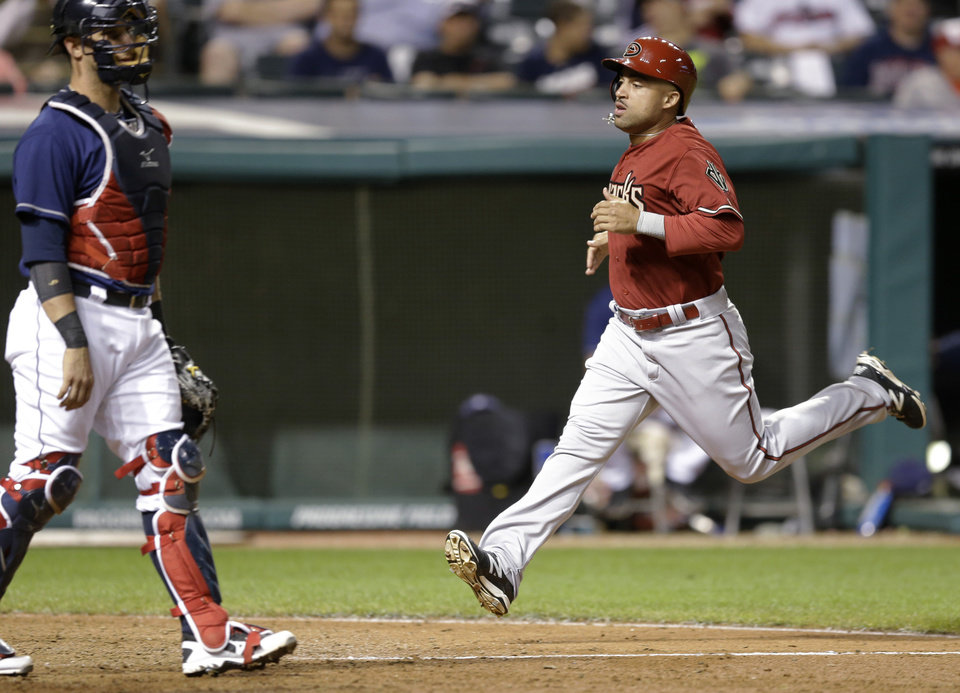 Photo - Arizona Diamondbacks' Xavier Paul, right, scores as Cleveland Indians catcher Yan Gomes waits in the 12th inning of the second baseball game of a doubleheader, Wednesday, Aug. 13, 2014, in Cleveland. The Diamondbacks defeated the Indians 1-0. (AP Photo/Tony Dejak)