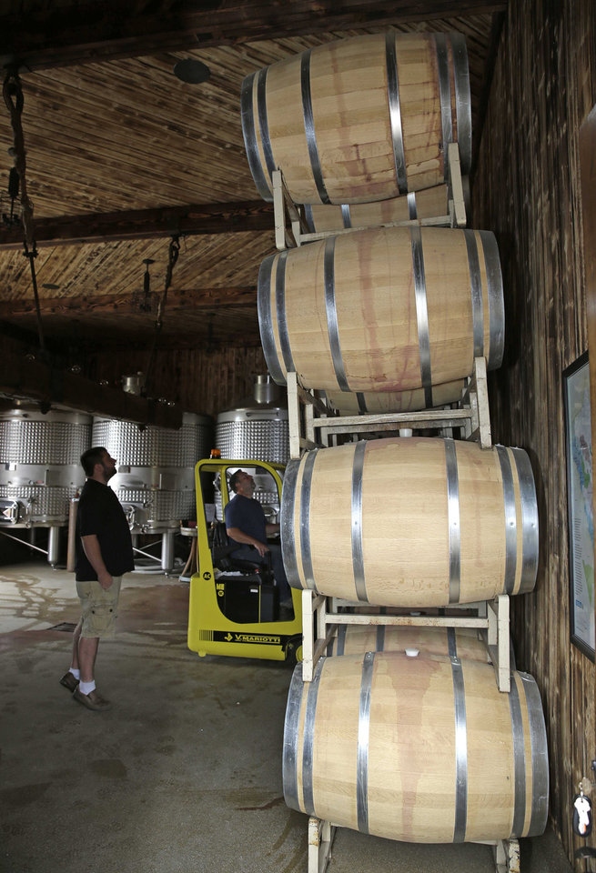 Photo - Tyler Dahl, left, and his father Robert work at removing wine barrels from a damaged rack following an earthquake at Dahl Vineyards Sunday, Aug. 24, 2014, in Yountville, Calif. A large earthquake caused significant damage and left at least three critically injured in California's northern Bay Area early Sunday, igniting fires, sending at least 87 people to a hospital, knocking out power to tens of thousands and sending residents running out of their homes in the darkness.  (AP Photo/Eric Risberg)
