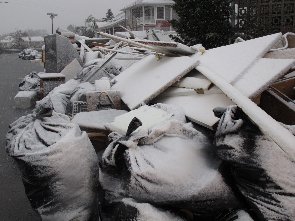 Snow covers debris piles as flood waters start to return to neighborhoods in Point Pleasant Beach, N.J., Wednesday Nov. 7, 2012, as a nor\'easter hits. The storm was threatening new damage to areas of the Jersey shore already devastated last week by Superstorm Sandy. (AP Photo/Wayne Parry)