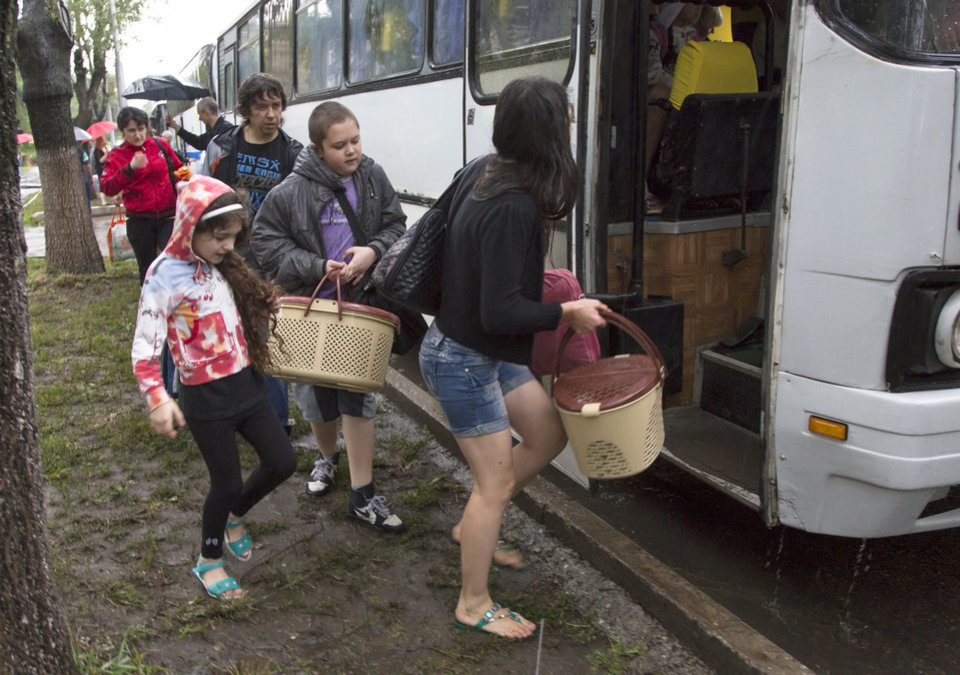 Photo - People board the bus as they depart as refugees to Russia in the city of Donetsk, eastern Ukraine Monday, July 14, 2014. Five busloads of Internally Displaced People from the towns of Slavyansk, Karlovka, Maryinka and Donetsk left here Monday morning for the Rostov region in Russia to ask for refugee status there.(AP Photo/Dmitry Lovetsky)