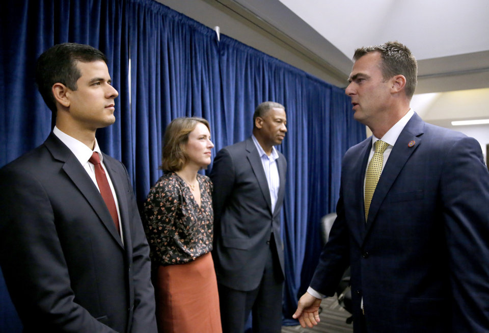 Photo - Gov. Kevin Stitt talks with Adam Luck after the Pardon and Parole Board read the names of 527 Oklahoma inmates recommend for commutation at the Kate Barnard Correctional Center in Oklahoma City, Friday, Nov. 1, 2019. [Sarah Phipps/The Oklahoman]