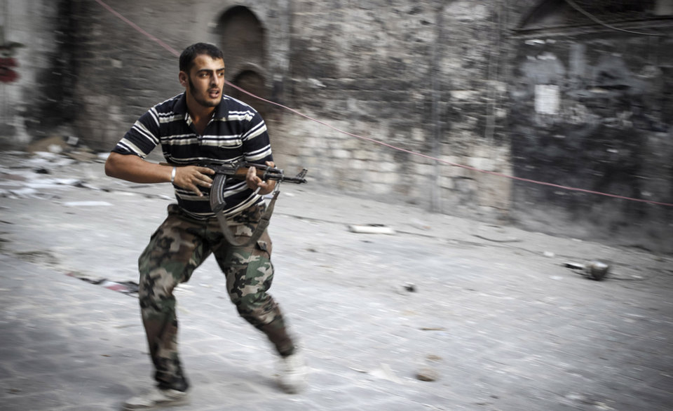 Photo -   In this Sunday, Nov. 4, 2012 photo, a Free Syrian Army fighter fires his weapon while running for cover in the Bab al-Nasr district of Aleppo, Syria. (AP Photo/Mustafa Karali)