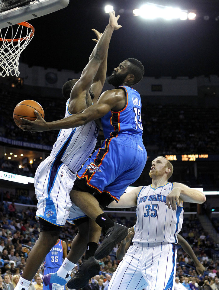Photo - Oklahoma City Thunder guard James Harden (13) passes around New Orleans Hornets centers Emeka Okafor (50) and Chris Kaman (35) during the first half of an NBA basketball game in New Orleans, Wednesday, Jan. 11, 2012. (AP Photo/Gerald Herbert)