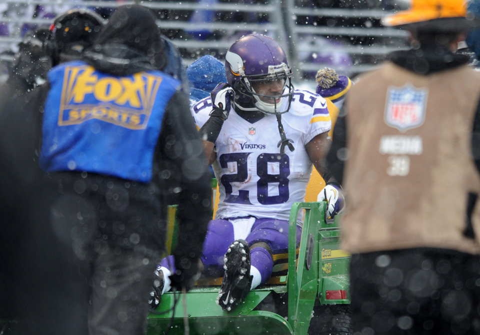Photo - Minnesota Vikings running back Adrian Peterson is carted off the field after injuring his ankle on a play in the second quarter of an NFL football game against the Baltimore Ravens, Sunday, Dec. 8, 2013, in Baltimore. (AP Photo/Gail Burton)
