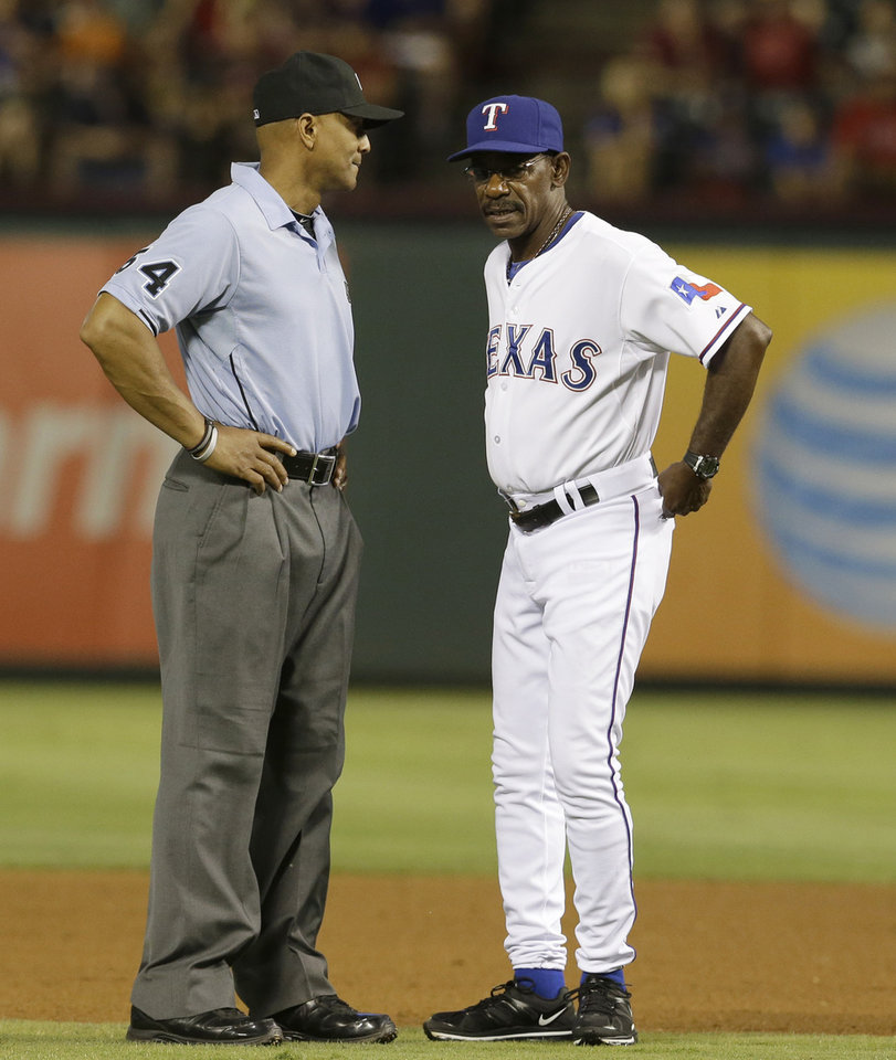 Photo - Texas Rangers manager Ron Washington, right, questions a call by second base umpire C.B. Bucknor (54) during the sixth inning of a baseball game against the Miami Marlins in Arlington, Texas, Tuesday, June 10, 2014. The Marlins won 8-5. (AP Photo/LM Otero)