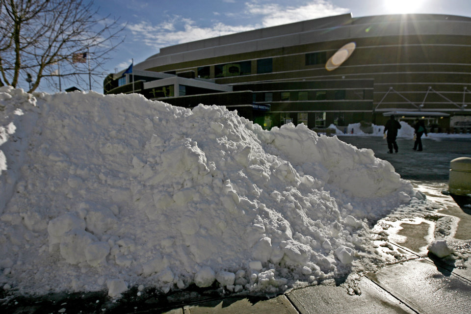 Photo - People walk past a pile of snow on the way to the Oklahoma City Arena on Wednesday, Feb. 2, 2011.  Photo by Bryan Terry, The Oklahoman