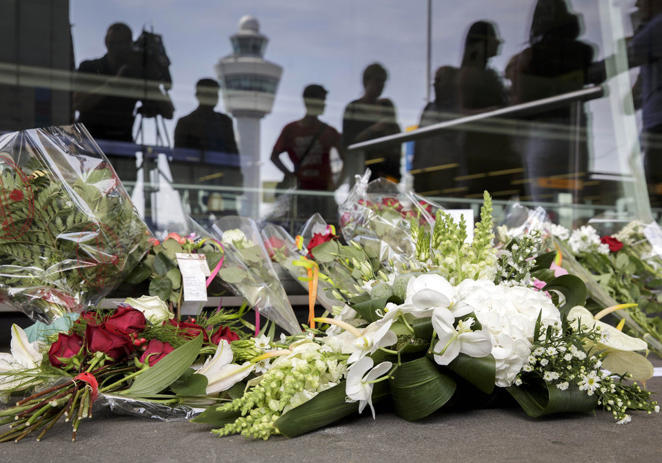 Photo - People place flowers outside Schiphol airport in Amsterdam, Friday, July 18, 2014. The attack on a Malaysian jetliner Thursday afternoon killed 298 people from nearly a dozen nations, more than half being Dutch, including vacationers, students and a large contingent of scientists heading to an AIDS conference in Australia.  (AP Photo/Phil Nijhuis)