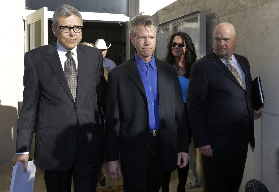 Photo - Entertainer Randy Travis, center, exits Grayson County Courthouse with his lawyer Larry Friedman, left, and an unidentified persons, right, Thursday, Jan. 31, 2013, in Sherman, Texas. Travis plead guilty to driving while intoxicated in a plea agreement with the court and will pay a $2,000 fine and serve a two year probation. (AP Photo/Tony Gutierrez)