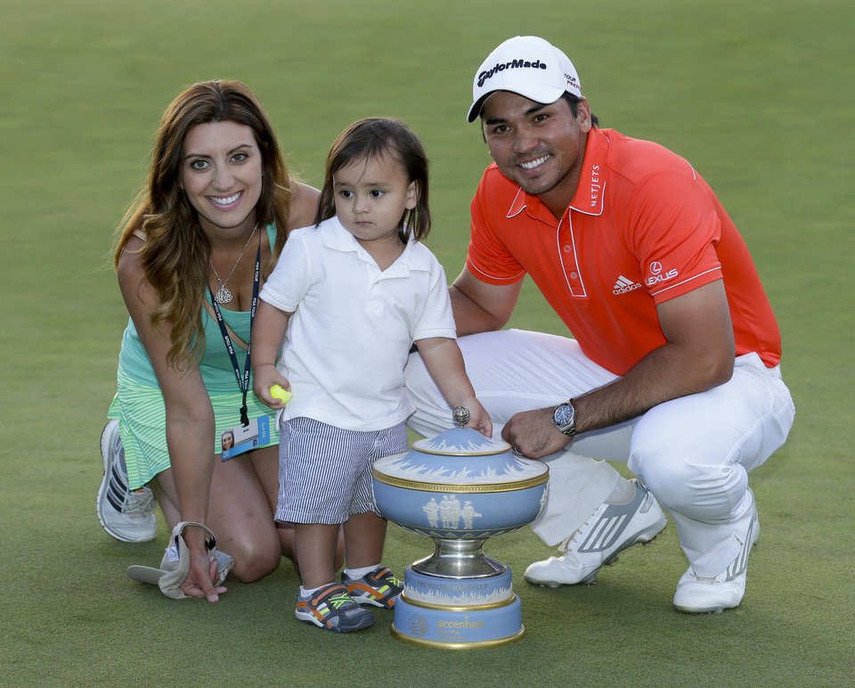 Photo - Jason Day, of Australia, right, his wife, Ellie, and son Dash, pose with the trophy after winning his championship match against Victor Dubuisson, of France, during the Match Play Championship golf tournament on Sunday, Feb. 23, 2014, in Marana, Ariz. (AP Photo/Ted S. Warren)