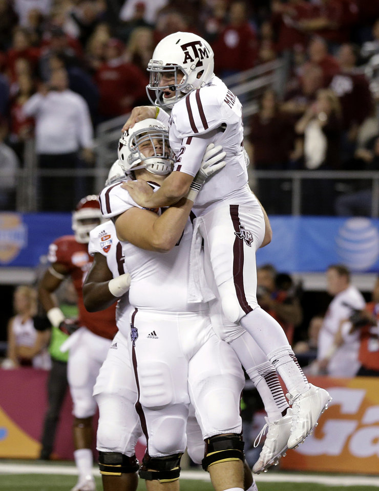 Photo - Texas A&M quarterback Johnny Manziel, right, celebrates his touchdown run with offensive linesman Luke Joeckel (76) in the first half of the Cotton Bowl NCAA college football game against Oklahoma on Friday, Jan. 4, 2013, in Arlington, Texas. (AP Photo/Tony Gutierrez)