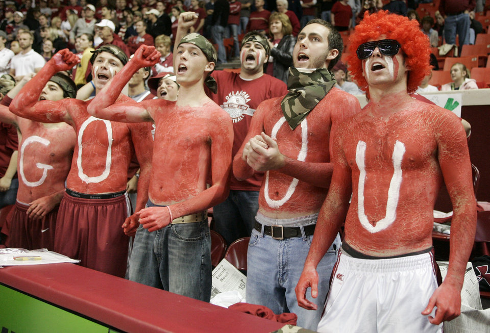 Photo - Fans, from left, from row, Tad Eccles, Elliott Edge, Kyle Hansel, Tim Heaton and Grant Harland, have painted their bodies University of Oklahoma red and cheer prior to an NCAA men's college basketball game featuring OU vs. American in Norman, Okla., Friday, Nov. 14, 2008. Oklahoma is encouraging students to come to the games with a new ticket policy. (AP Photo/Sue Ogrocki) ORG XMIT: OKSO106