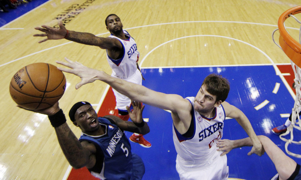 Minnesota Timberwolves' Josh Howard (5) shoots as Philadelphia 76ers' Spencer Hawes, right, and Dorell Wright defend in the first half of an NBA basketball game, Tuesday, Dec. 4, 2012, in Philadelphia. (AP Photo/Matt Slocum)