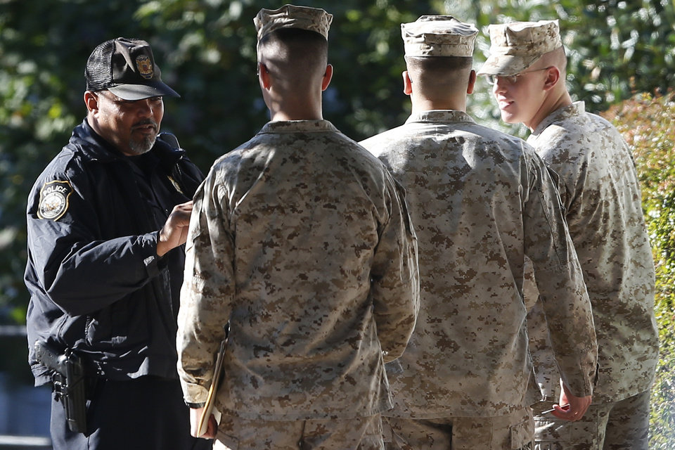 Photo - Military personnel have their identification checked after they enter the Washington Navy Yard Thursday, Sept. 19, 2013. The Washington Navy Yard began returning to nearly normal operations three days after it was the scene of a mass shooting in which a gunman killed 12 people. (AP Photo/Charles Dharapak)