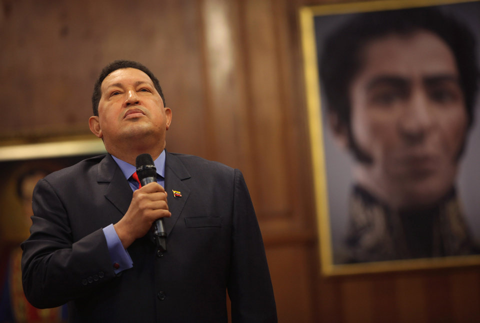 Backdropped by a portrait of independence hero Simon Bolivar, Venezuela's President Hugo Chavez talks during a press conference at the Miraflores palace in Caracas, Venezuela, Tuesday, Oct. 9, 2012. The 58-year-old former military officer Chavez won his fourth consecutive presidential bid Sunday and shows no signs of ballot fatigue. (AP Photo/Rodrigo Abd)