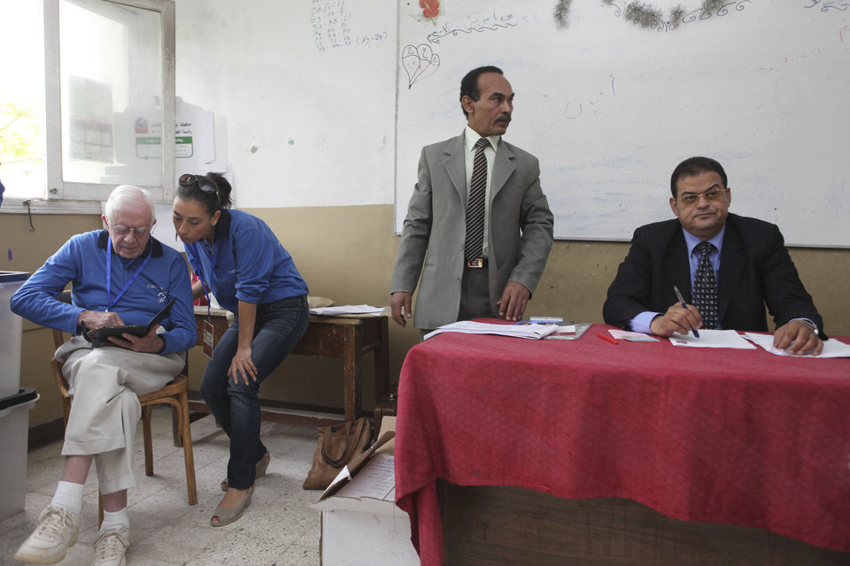 Photo -   Former U.S. President Jimmy Carter, left, consults with a member of the Carter Center inside a polling station in the Sayeda Aisha neighborhood of Cairo, Egypt, Wednesday, May 23, 2012. The Carter Center is in Egypt to monitor the presidential elections. Egyptians went to the polls on Wednesday morning to elect a new president after the fall of ex-President Hosni Mubarak last year.(AP Photo/Thomas Hartwell)