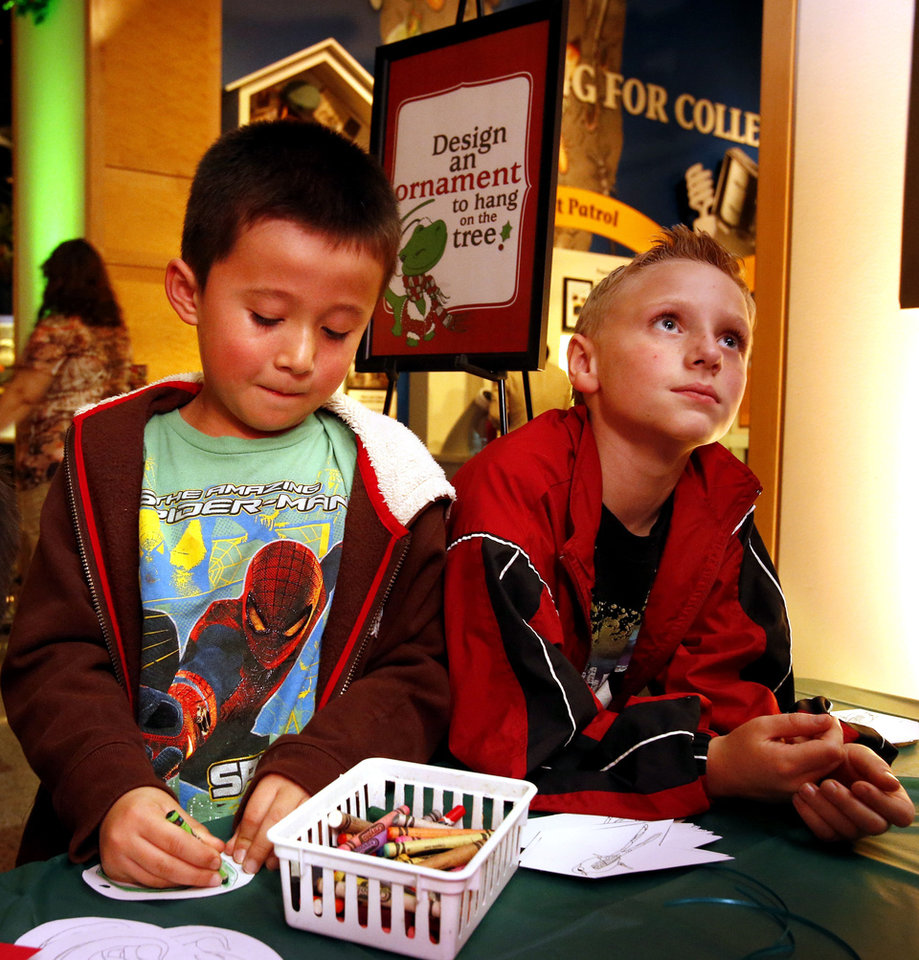 Hayden Nelson, 6, left, and Weston Hutchins, 8, design ornaments during the �Holiday Happening� on Thursday at the Sam Noble Oklahoma Museum of Natural History. PHOTOS BY STEVE SISNEY, THE OKLAHOMAN
