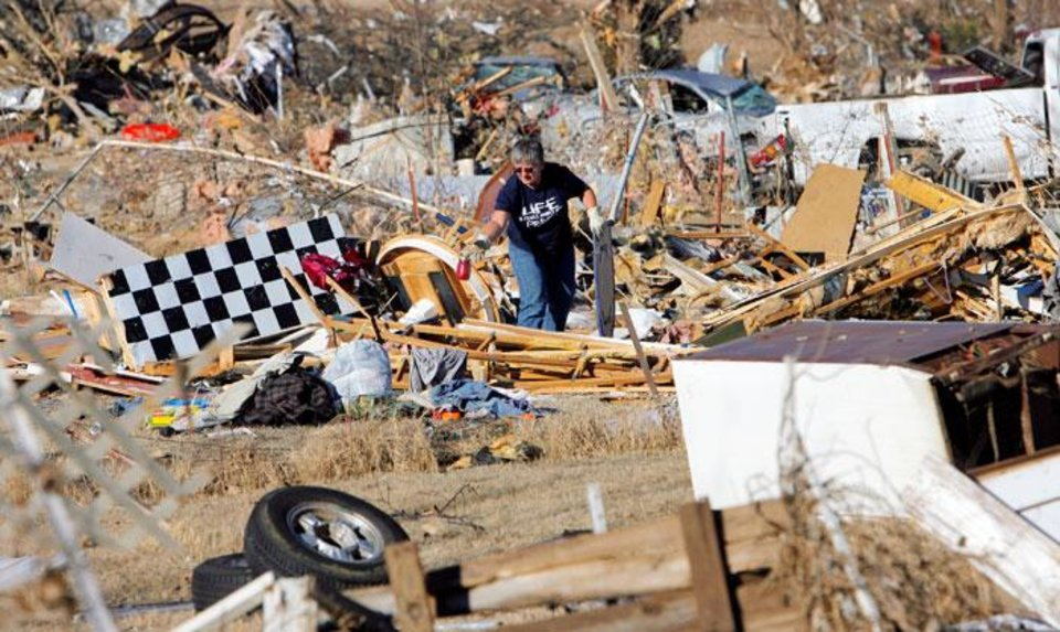 Photo -  Tammie Rose searches for items to salvage from the destroyed mobile home in which her daughter, Shawna Inlow, used to live in Lone Grove, Okla., Wednesday, February 11, 2009. On Tuesday, February 10, 2009, a tornado moved through Lone Grove killing at least nine people. Inlow and her three boys were able to ride  out the storm safely in Rose's cellar. BY NATE BILLINGS, THE OKLAHOMAN