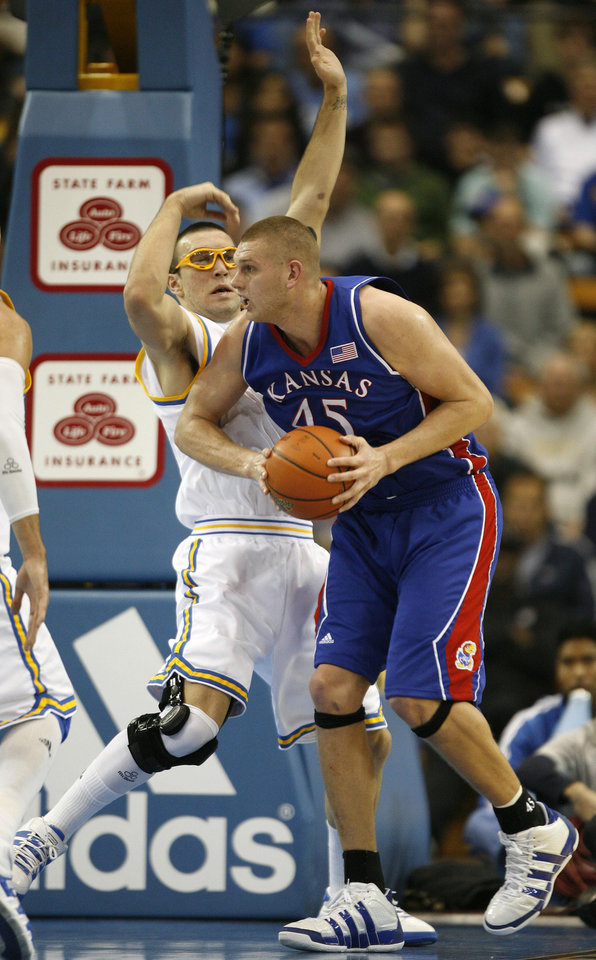 Photo - Kansas center Cole Aldrich (45) holds onto the ball while defended by UCLA forward Reeves Nelson in the second half of their NCAA college basketball game in Los Angeles on Sunday, Dec. 6, 2009. Kansas won 73-61. (AP Photo/Jason Redmond) ORG XMIT: CAJR110