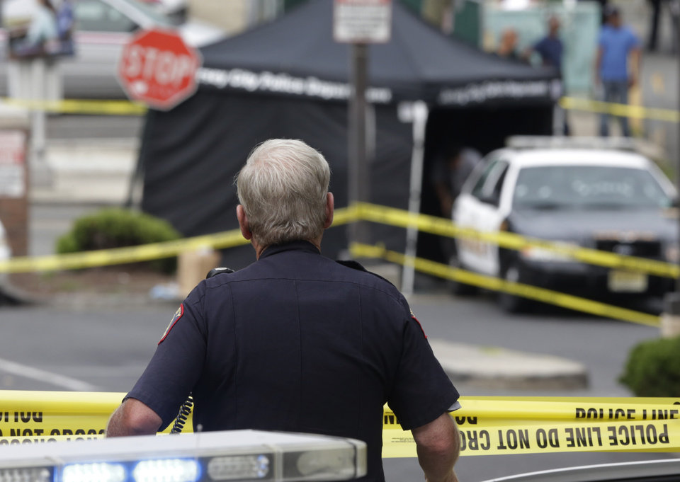 Photo - A Jersey City Police Department officer stands guard on the perimeter of a crime scene where an officer was shot and killed while responding to a call at a 24-hour pharmacy, Sunday, July 13, 2014, in Jersey City, N.J.  Officer Melvin Santiago was shot in the head while still in his police vehicle as he and his partner responded to an armed robbery call  at about 4.a.m., Jersey City Mayor Steven Fulop said in a statement.  Fulop said officers responding to the robbery call shot and killed the man who shot Santiago. He was not immediately identified.(AP Photo/Julio Cortez)