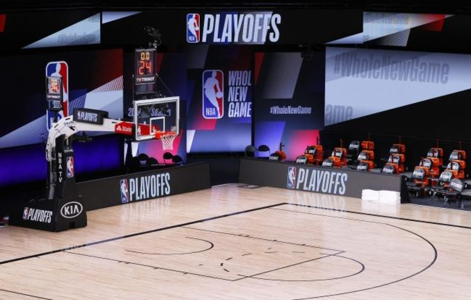 Photo -  An empty court and bench are shown with the #WholeNewGame signage following the scheduled start time of Game 5 of an NBA basketball first-round playoff series, Wednesday, Aug. 26, 2020, in Lake Buena Vista, Fla. NBA players made their strongest statement yet against racial injustice Wednesday when the Milwaukee Bucks didnþÄôt take the floor for their playoff game against the Orlando Magic. (Kevin C. Cox/Pool Photo via AP)