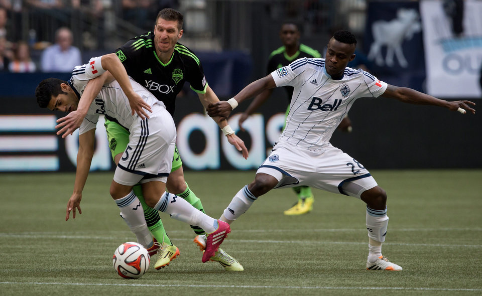 Photo - Vancouver Whitecaps' Matias Laba, left, of Argentina, Seattle Sounders' Kenny Cooper, center, and Whitecaps' Gershon Koffie, of Ghana, battle for the ball during the first half of an MLS soccer game in Vancouver, British Columbia, Saturday, May 24, 2014. (AP Photo/The Canadian Press, Darryl Dyck)