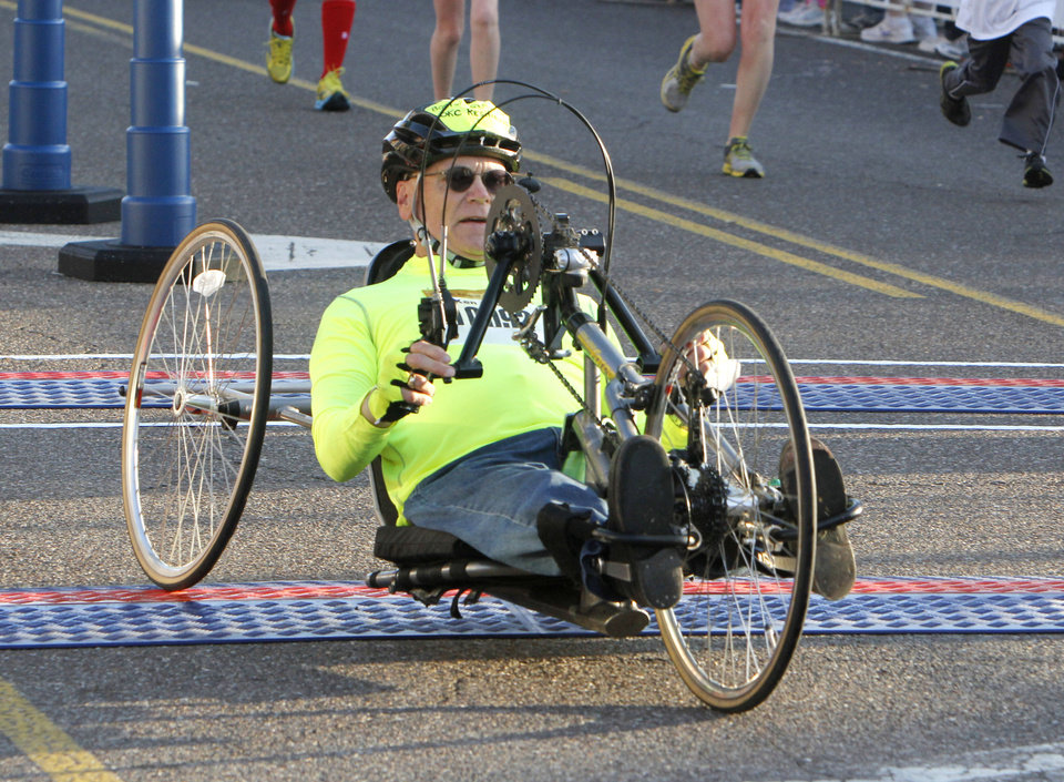 Photo - Ada resident Ken Lewis crosses the finish line of the half-marathon in a wheelchair during the Oklahoma City Memorial Marathon in Oklahoma City, Sunday, April 28, 2013,  By Paul Hellstern, The Oklahoman