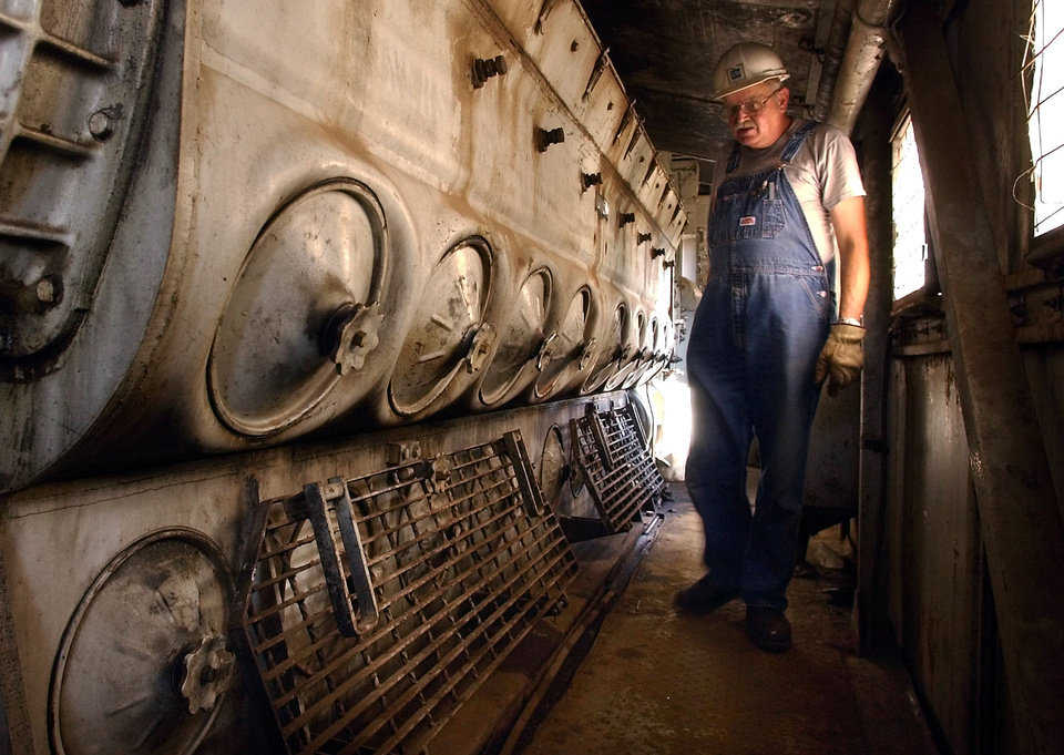 Photo - Oklahoma City, OK; Saturday July 25. 2003:   Jim Murray, Oklahoma City volunteer, walks beside the 16-cylinder F9 diesel power plant inside an engine at the Oklahoma Railway Museum. The General Motors engine requires 200 gallons of oil.     Steve Sisney - The Oklahoman