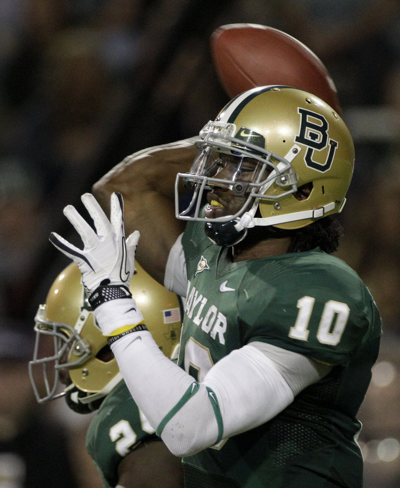 Photo - Baylor quarterback Robert Griffin III (10) passes against Oklahoma in the first half of an NCAA college football game on Saturday, Nov. 19, 2011, in Waco, Texas. (AP Photo/Tony Gutierrez)