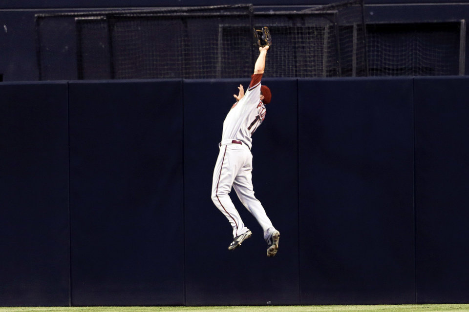 Photo - Arizona Diamondbacks center fielder A.J. Pollock makes a leaping catch at the wall, robbing San Diego Padres' Rene Rivera of a hit, during the third inning of a baseball game Thursday, Sept. 4, 2014, in San Diego. (AP Photo/Gregory Bull)