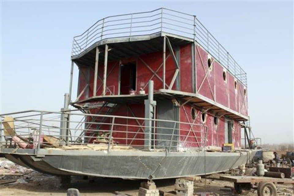 In this photo taken Nov. 24, 2012, an ark-like vessel which belongs to Lu Zhenghai sits while still under construction in China's northwest Xinjiang Uyghur Autonomous Region.  Lu Zhenghai is one of at least two men in China predicting a world-ending flood, come Dec. 21, the fateful day many believe the Maya set as the conclusion of their 5,125-year long-count calendar. Zhenghai has spent his life savings building the 70-foot-by-50-foot vessel powered by three diesel engines, according to state media. (AP Photo/ANPF-Chen Jiansheng)