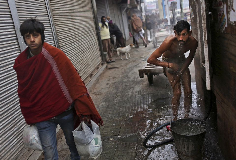 An Indian laborer washes himself at an outdoor tap as another walks by wrapped in a shawl on a cold winter morning in New Delhi, India, Monday, Jan. 7, 2013. North India continues to face below average weather conditions with dense fog affecting flights and trains. More than 100 people have died of exposure as northern India deals with historically cold temperatures. (AP Photo/Kevin Frayer)