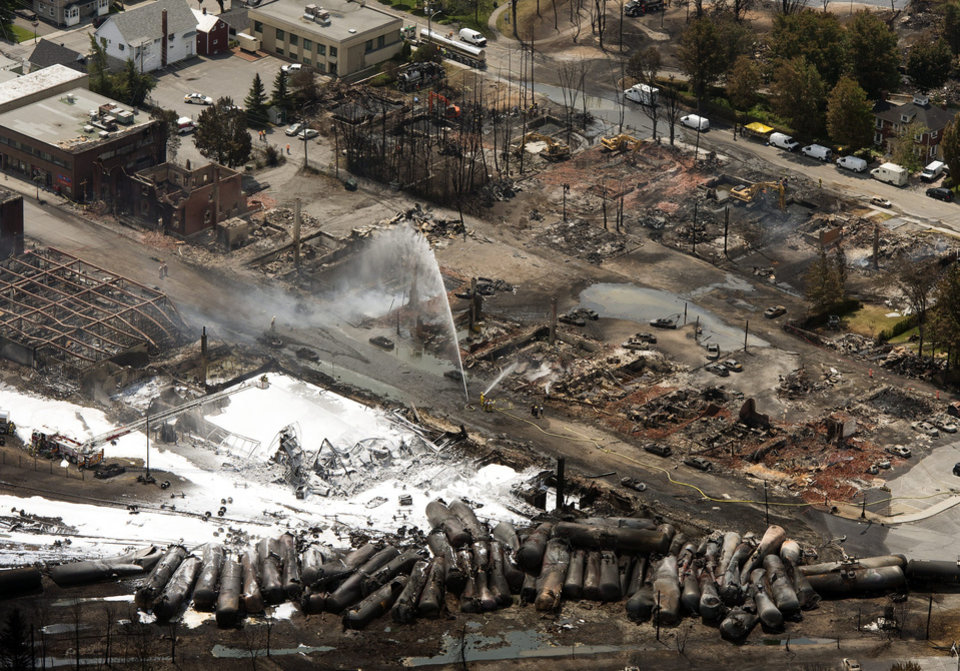 The downtown core lays in ruins as fire fighters continue to water smoldering rubble Sunday, July 7, 2013, in Lac Megantic, Quebec, after a train derailed ignited tanker cars carrying crude oil.   The runaway train derailed, causing explosions and fires that destroyed the downtown district.  (AP Photo/THE CANADIAN PRESS,Ryan Remiorz)